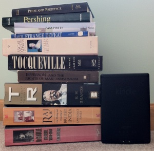 Print vs. E-book. [Photo by me, 2014.] Note: I have no idea how the 3rd book from the top got into that pile. ;-)