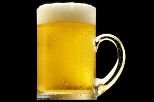 Free Stock Photo: A mug of golden beer with a white froth, against a black background.
