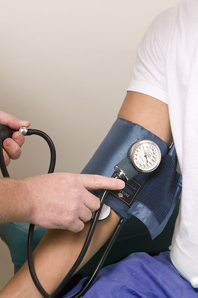 Free Stock Photo: This image depicts a healthcare practitioner in the process of conducting a blood pressure examination upon a seated male patient in a clinical setting.