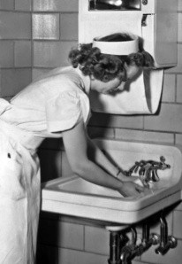 Free Stock Photo: This historic 1930s photograph depicted a nurse in a starched cap and uniform, washing her hands in an improved, bacteria-controled environment. The improvements included the tiled walls, and the towel machine above the sink.