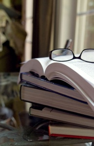 Free Stock Photo: This image depicts a stack of books, topped by pair of eyeglasses.