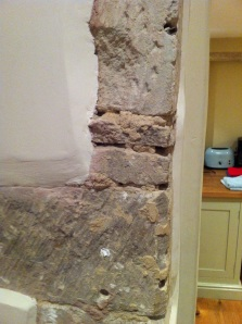 Exposed stone, underneath the plaster, on the wall next to the entrance to the kitchen. Turleigh, Wiltshire. [Photo by me, 2014.]