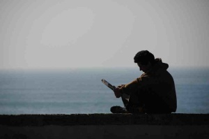 Free Stock Photo: Silhouette of a man reading by the ocean