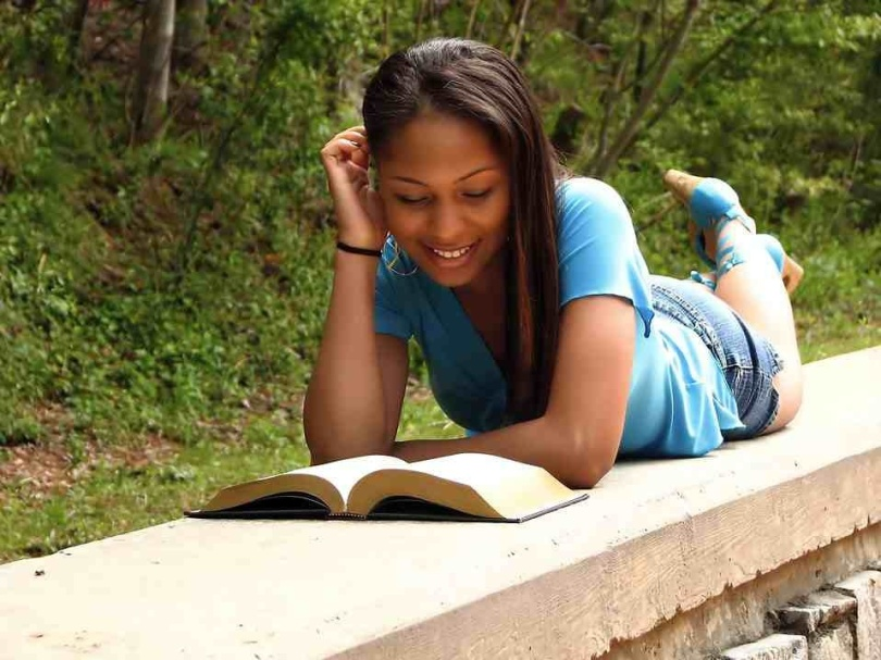 Free Stock Photo: A beautiful African American teen girl reading a book on a stone wall in the woods.
