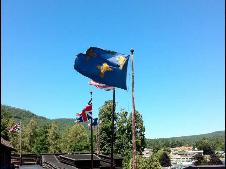Now THIS is upstate New York. Flags fluttering from the rebuilt Fort William Henry, on Lake George. Note which they are: France'ss pre-revolutionary Fleur-de -lis, Great Britain's Union Jack, and today's U.S. Stars and Stripes. Two empires - France and Britain - fought over this spot in the 1750s. Britain won. Twenty years later, Americans then threw the British out.... with help from the French. [Photo by me, 2013.]