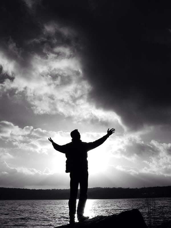 Free Stock Photo: A silhouette of a man reaching towards the sky.