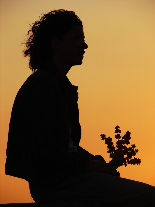 Free Stock Photo: Silhouette of a woman holding flowers before a sunset.