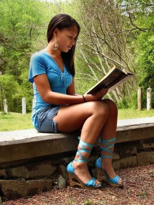 Free Stock Photo: A beautiful African American teen girl reading a book on a stone wall outside.