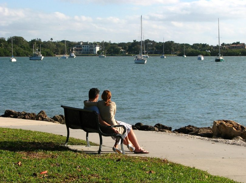 Free Stock Photo: A couple sitting on a bench overlooking the ocean.