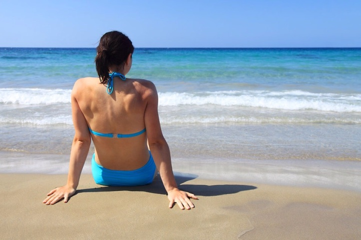 Free Stock Photo: A beautiful woman sitting on the beach looking at the ocean.