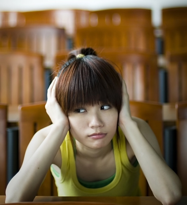 Free Stock Photo: A beautiful Chinese girl sitting tired at a desk.
