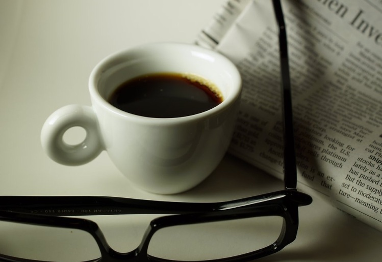 Free Stock Photo: A cup of coffee with a newspaper and eye glasses.