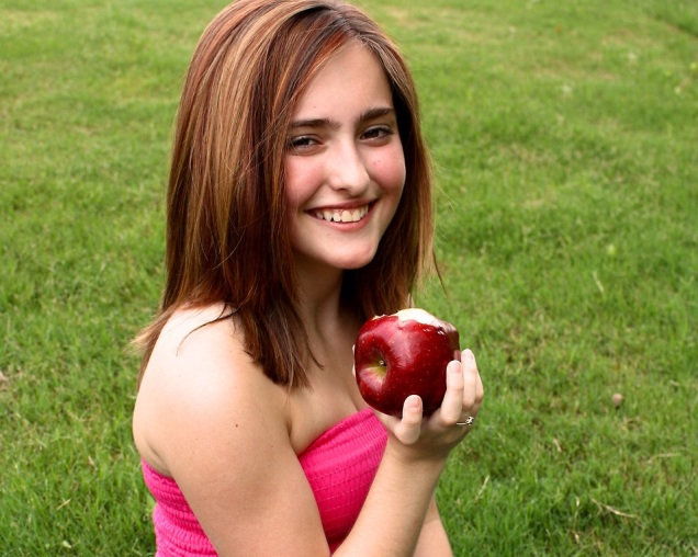 Free Stock Photo: A beautiful young girl holding an apple in the grass.