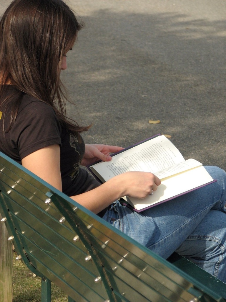 Free Stock Photo: Teenage girl reading a book on a park bench.