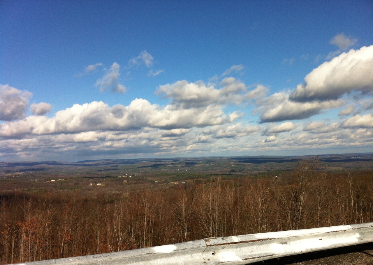 From a parking viewpoint on Route 23, which winds westwards up into the Catskills from the north-south New York State Thruway (I-87). New York State is spread out immediately below. Off in the distance, to the center and right, you can see to Vermont, Massachusetts and Connecticut. [Photo by me, 2015.]