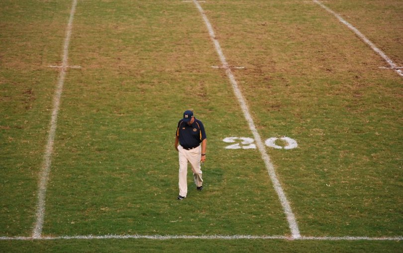 Free Stock Photo: A football coach walking on an empty football field.