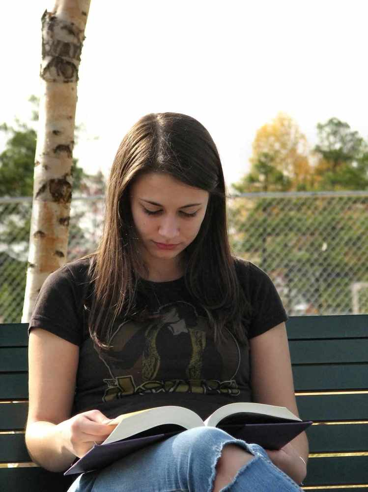 Free Stock Photo: Closeup of a teenage girl reading a book on a park bench.