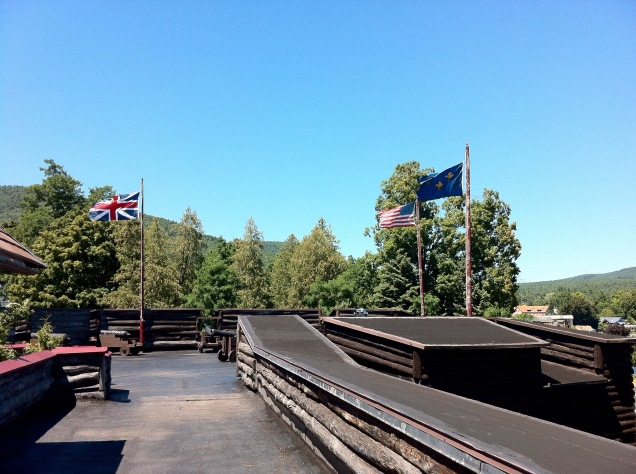 Flags of Great Britain, the independent U.S.A., and pre-revolutionary France, flying over the recreated Fort William Henry, on the edge of Lake George, New York. [Photo by me, 2013.]