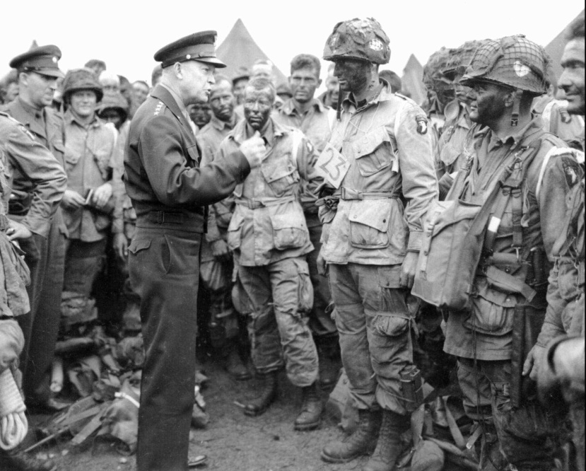 The now famous photograph: General Eisenhower talking with U.S. paratroopers at a take-off airfield, southern England, evening, June 5, 1944. One soldier there later said that Eisenhower had looked so stressed and worried that they all felt they had to reassure him everything would be fine. [U.S Army photo. Public domain.]